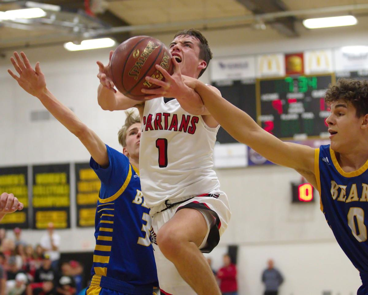 Kent Earhart (1) of East Nicolaus is fouled while going to the basket by Cameron Collard (0) in the first half in the D5 title game at Butte Valley Friday night (Photo by Eddie Saltzman)