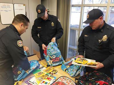 Fire Department prepare backpacks of school supplies
