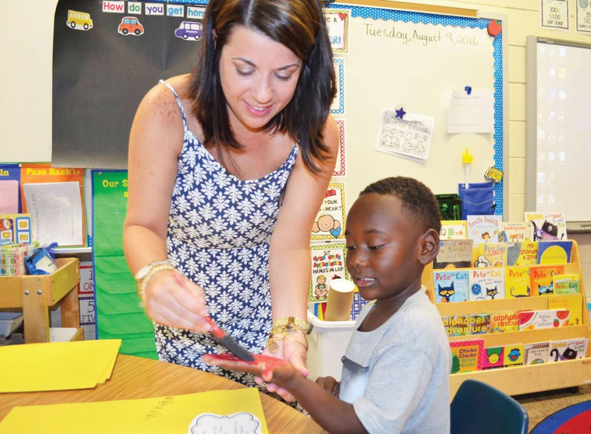 Contributed/Auburn City Schools Brandy Wynn, kindergarten teacher at Richland Elementary School, helps student Ashtjon Brown with an art project.