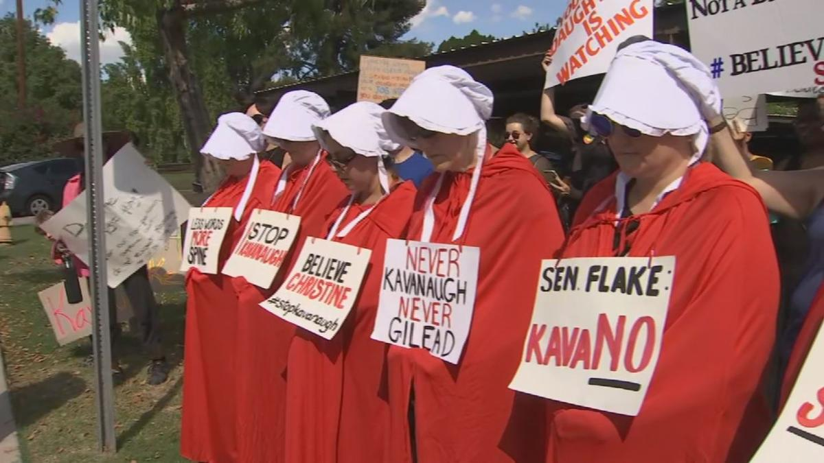 Protesters in costumes from 'The Handmaid's Tale' gather outside Sen. Flake's Phoenix office.