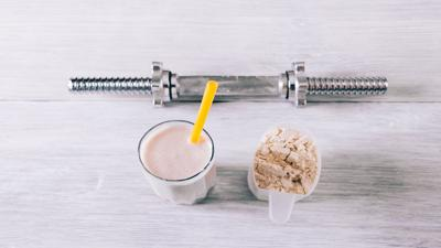 Protein cocktail in a glass, scoop and dumbbell on a white woode
