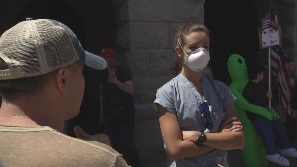 Woman in scrubs standing in solidarity against protesters Monday