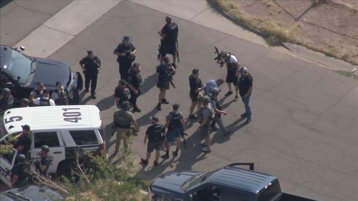 Officers detain a man during a police situation in east Mesa