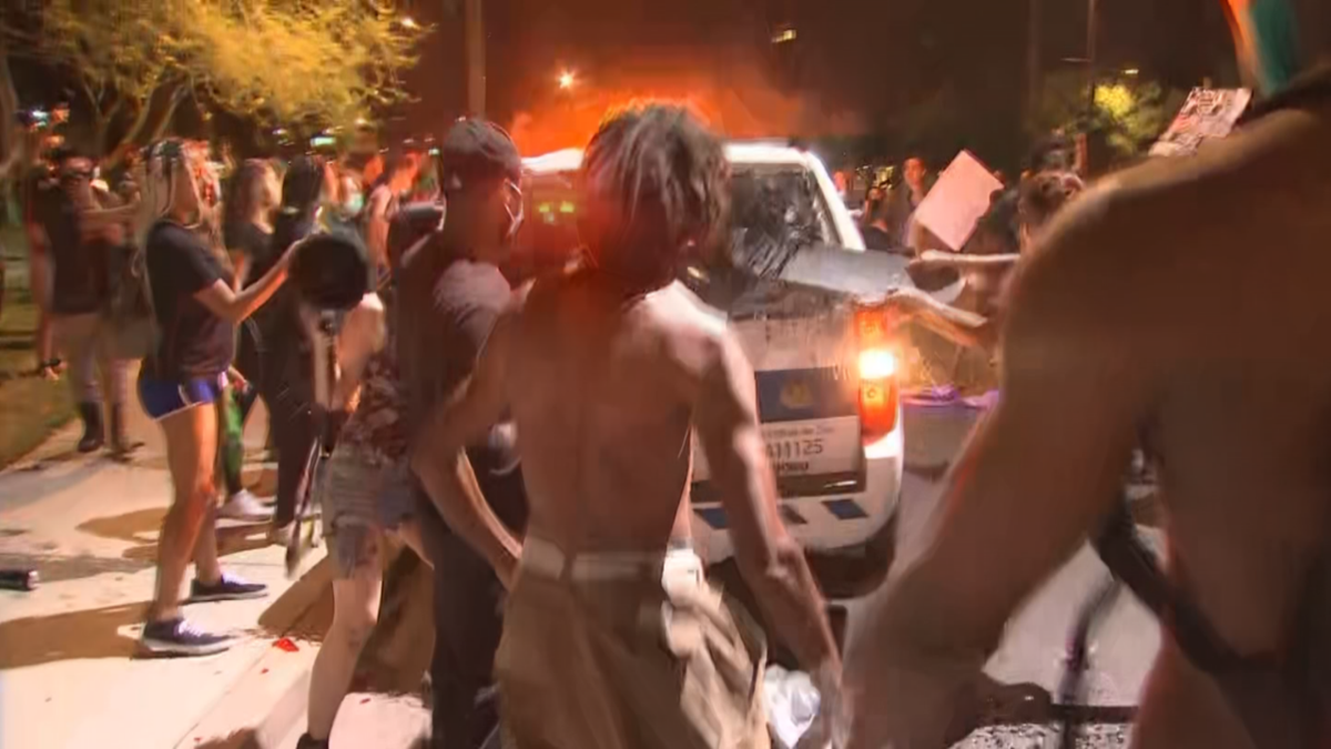 Protester smashes back window of Phoenix police SUV
