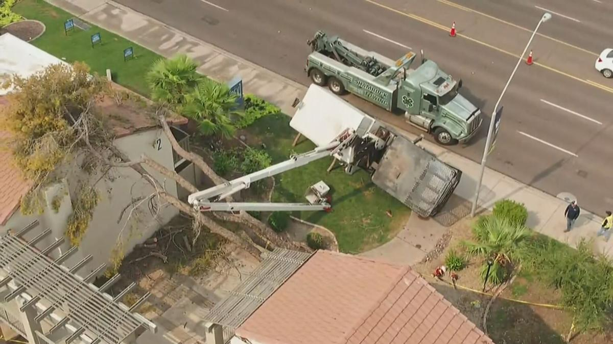 Crane tips while hoisting downed tree in Tempe