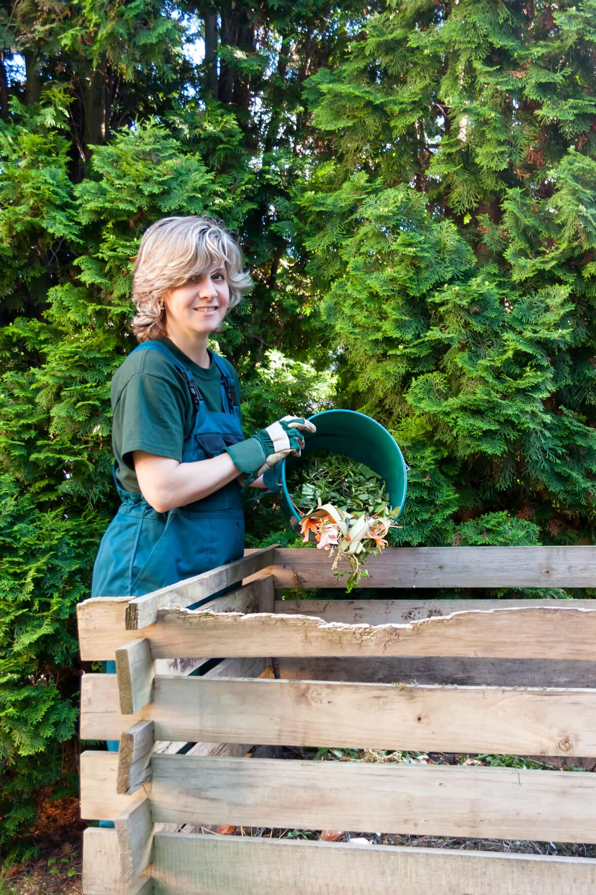 Young, smiling caucasian female emptying a bucketful of compost to the compost pile