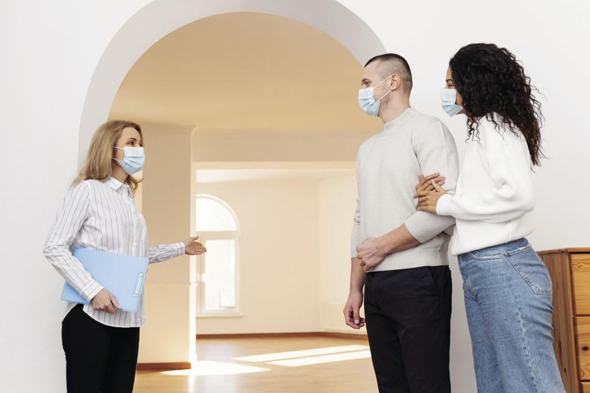 female-realtor-with-medical-mask-showing-couple-new-house.jpg