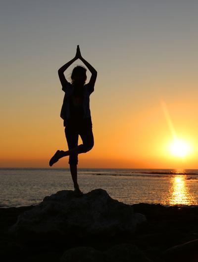 Girl Practicing Yoga at sunset