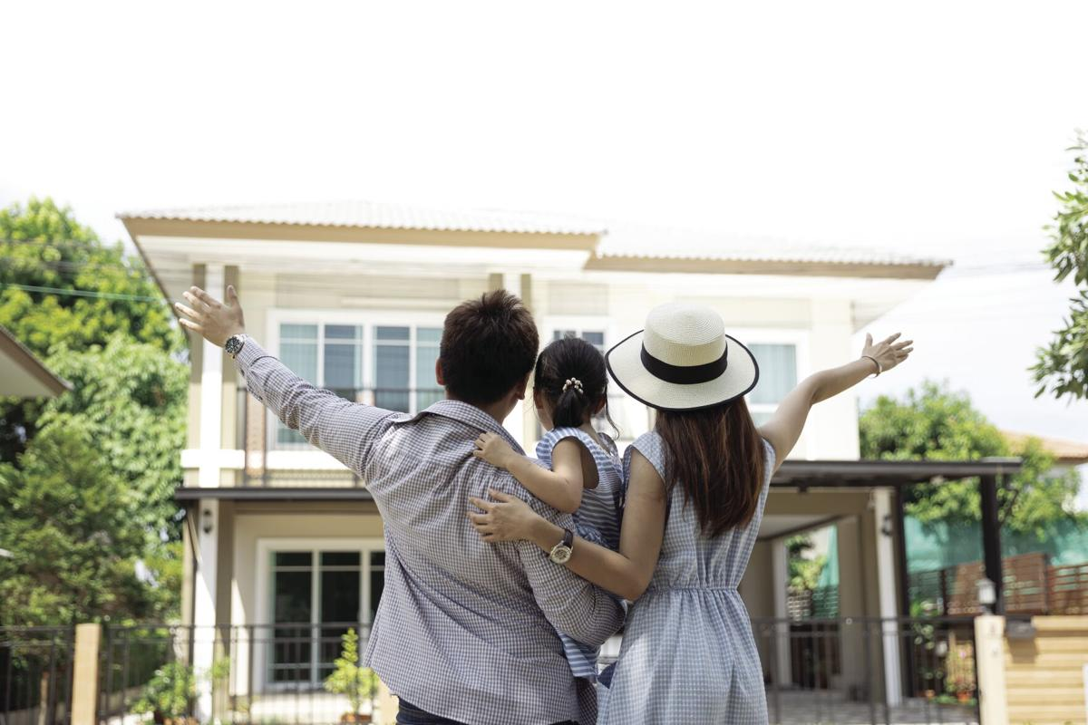 Happy Asian family. Father, mother and daughter near new home. Real estate background with copy space