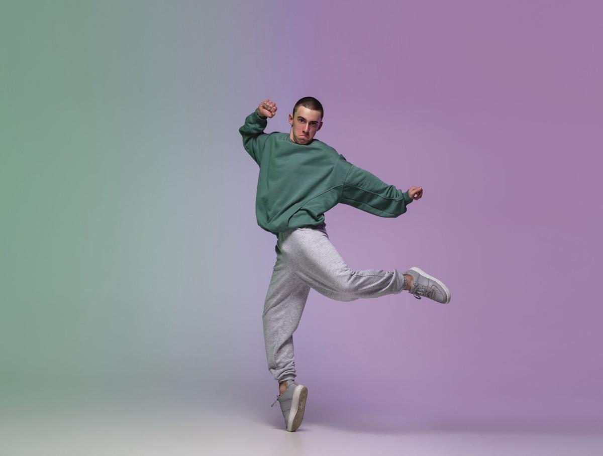 Boy dancing hip-hop in stylish clothes on gradient background at dance hall in neon light.