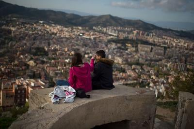 A couple enjoy the views over the city from old anti-aircraft batteries built to defend the city during the Spanish Civil war on April 10, 2015 in Barcelona, Spain.