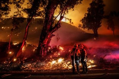 In this file photo, Firefighters monitor a controlled burn as they work to contain the spread of the Maria fire in Santa Paula, CA, on Nov. 1, 2019. Fire authorities are growing increasingly concerned over their ability to muster a large, healthy force of firefighters in the face of COVID-19.