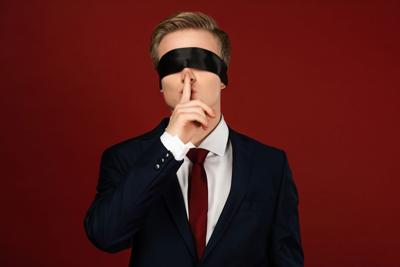 KYIV, UKRAINE - OCTOBER 18, 2019: man imitating Donald Trump with blindfold on eyes showing shh gesture on red background