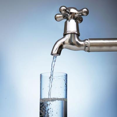 water is poured into a glass from the tap
