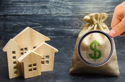 A bag with money and wooden houses. Selling a house. Apartment purchase. Real estate market. Rental housing for rent. Home prices. Mortgage interest. Purchase demand. Property valuation. Insurance