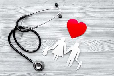 Choose health insurance. Stethoscope, paper heart and silhouette of family on grey wooden background top view