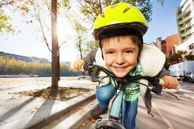 Smiling boy in safety helmet riding his bike