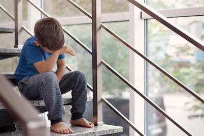 Little boy crying on stairs indoors. Domestic violence concept