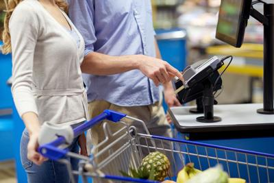 couple buying food at grocery self-checkout