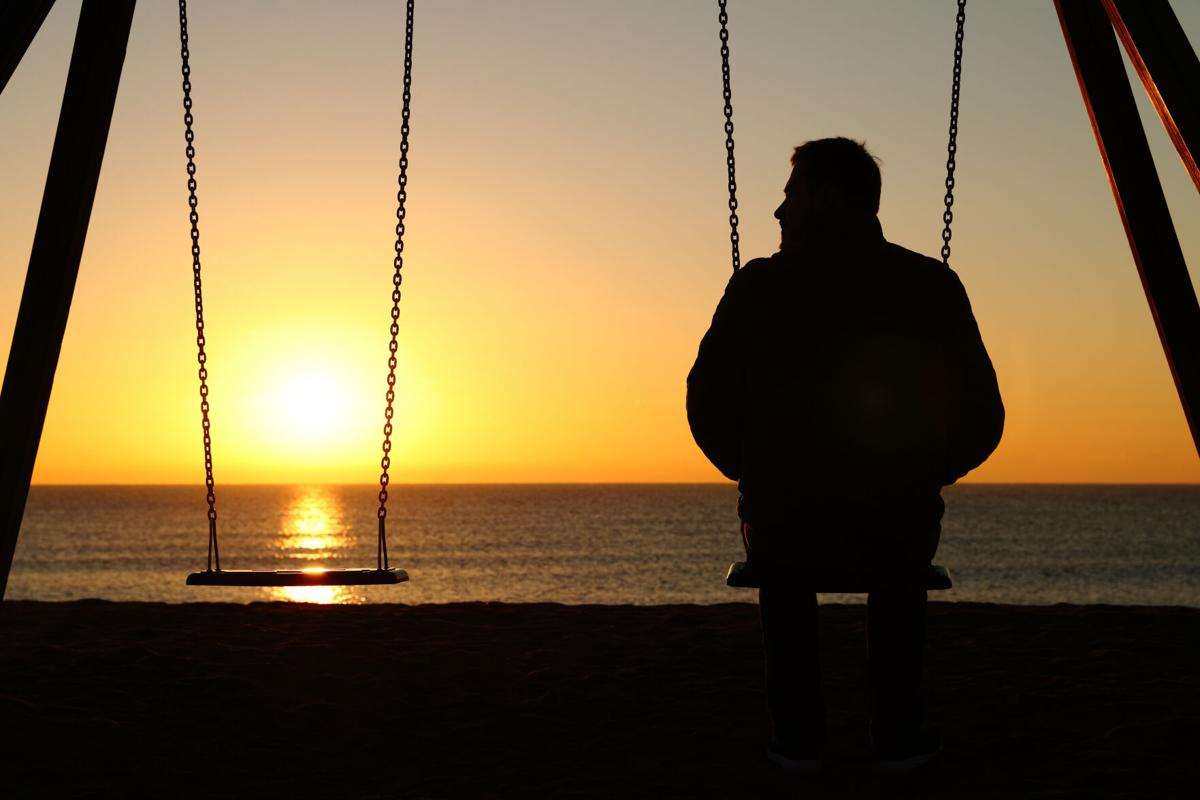 Man alone on a swing looking at empty seat