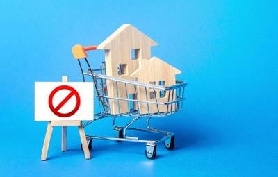 Houses in a shopping cart and easel red prohibition sign NO. Inaccessibility, lack housing, deficit. Seizure, freezing of assets by a bank, court. Expensive maintenance, impossibility of restoration