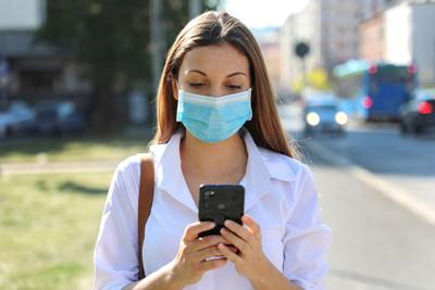 COVID-19 Pandemic Coronavirus Young Woman Wearing Surgical Mask Using Smart Phone App in City Street to Aid Contact Tracing in Response to the 2019-20 Coronavirus Pandemic (copy)