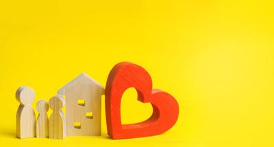 family is standing near the house. House with a heart. lovers. Affordable housing for young families. Accommodation for lovers of couples. Valentine's day. real estate. yellow background. place for text