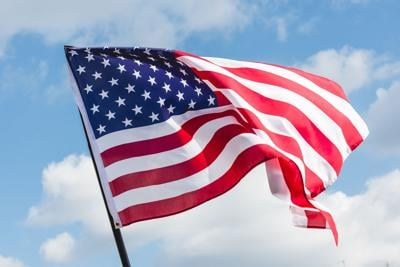 low angle view of stars and stripes on american flag against blue sky