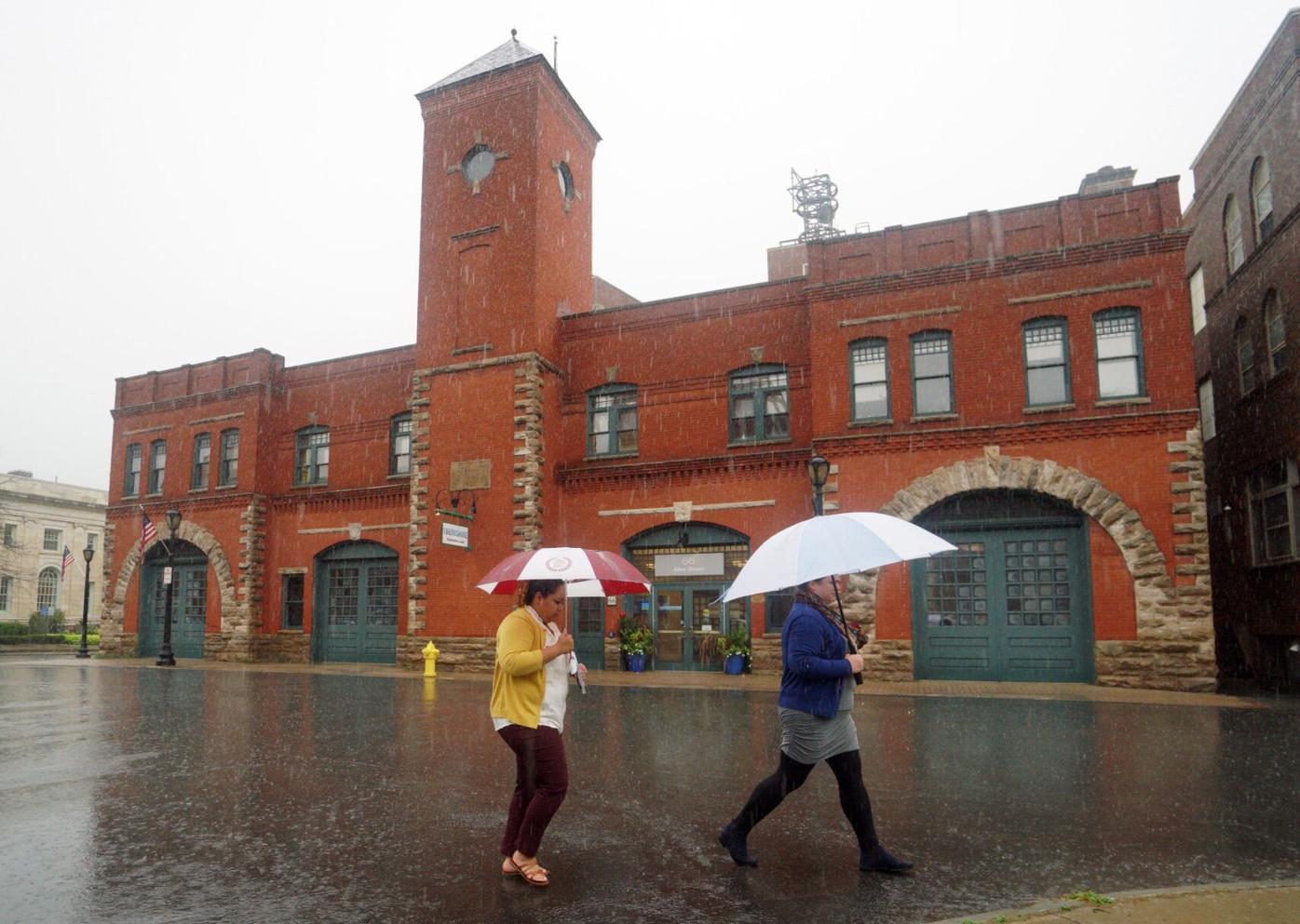 Two women walking with umbrellas in rain (copy)