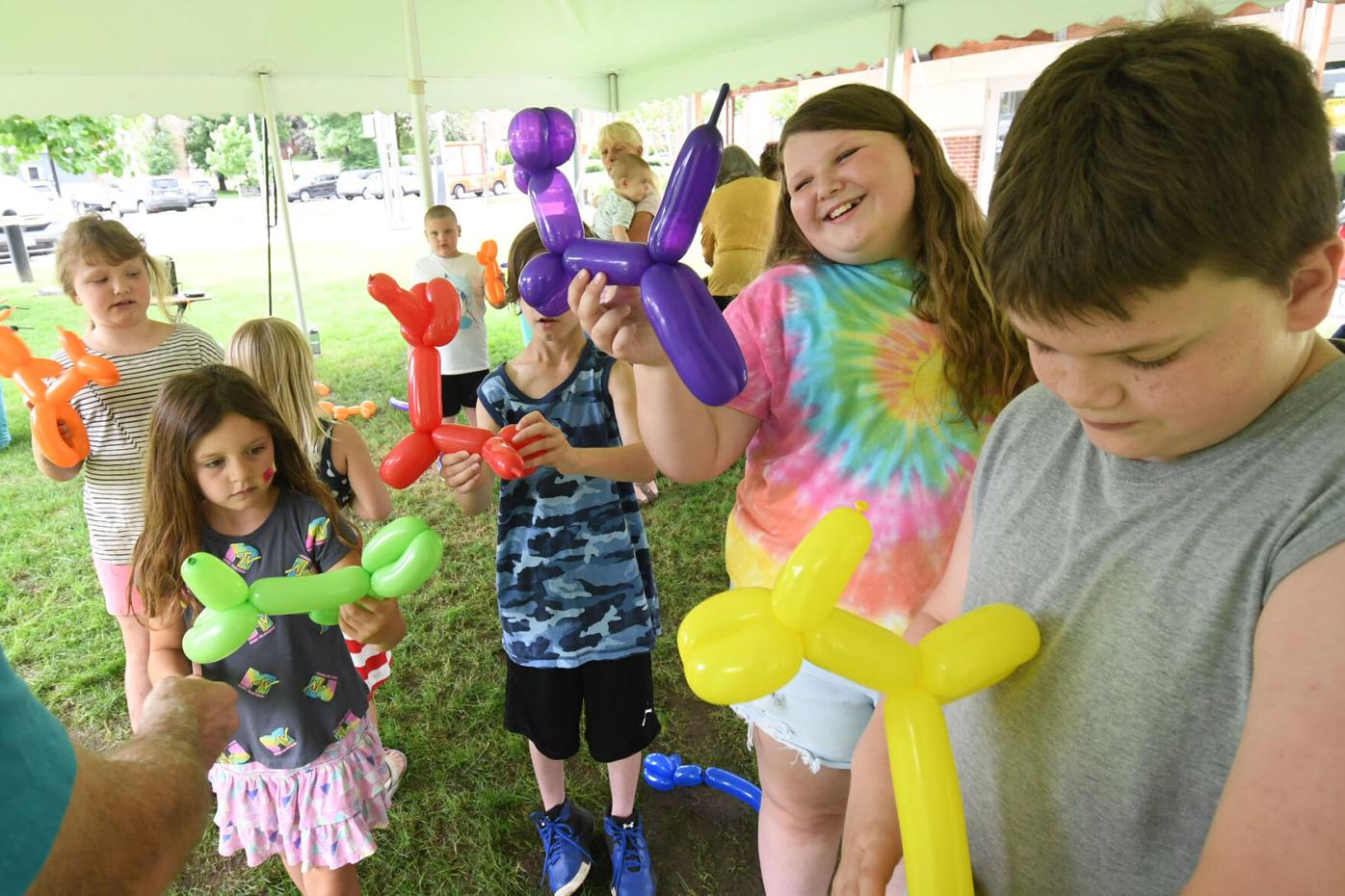 Children hold up their balloon animals which are shaped like a dog