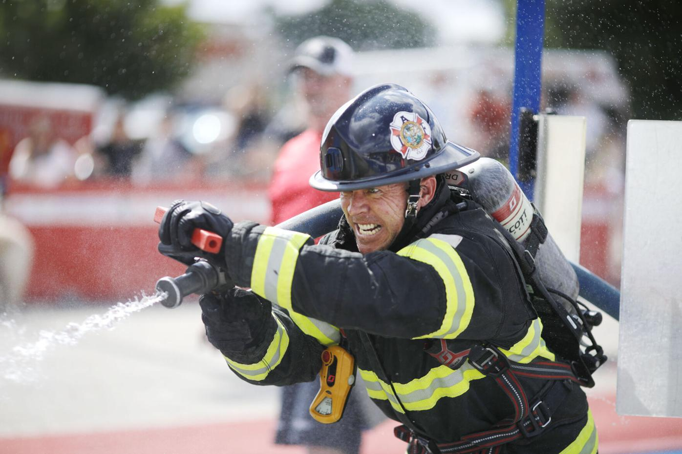 Firefighter grits teeth and sprays fire hose