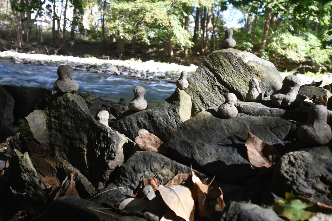 Figures sit on rocks along the river
