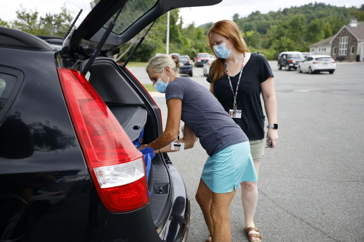 Ashli Minor and Hannah Paterson load grocery bags into car