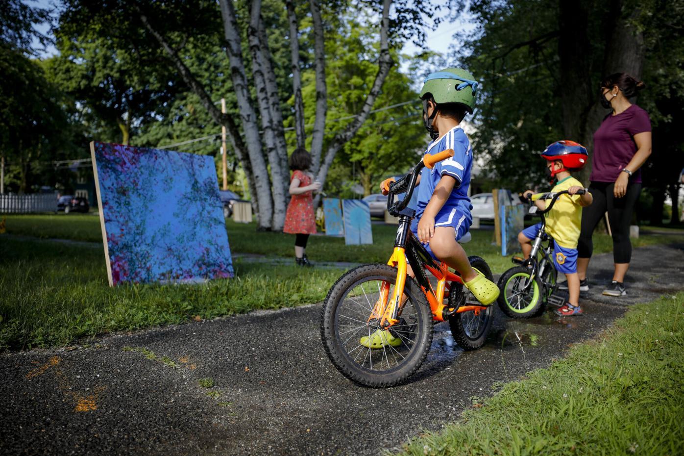 Kids on bikes look at art