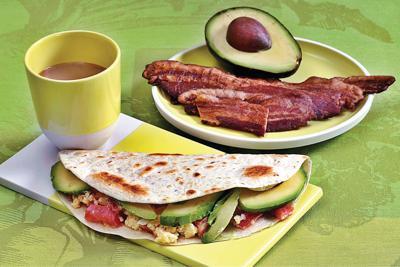 Mix cheesy eggs, ripe avocado for a yummy breakfast taco