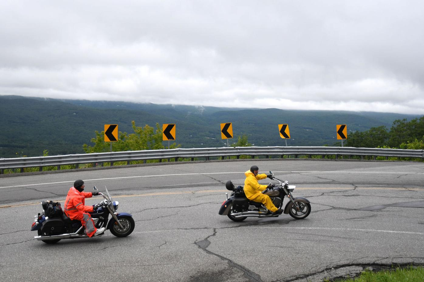 Two motorcycles drive up a hairpin turn