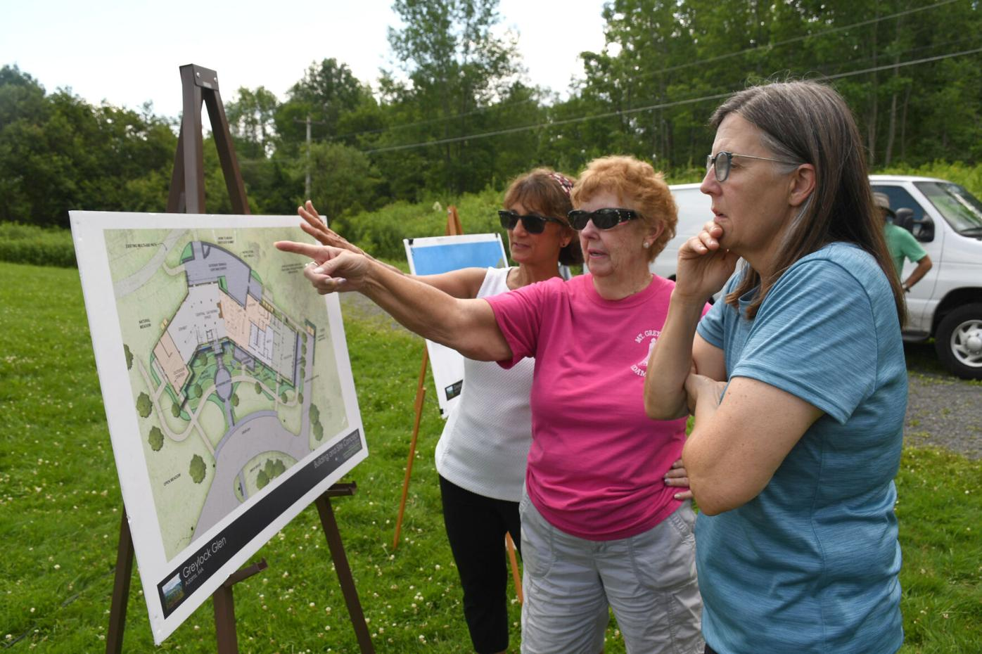Three women look at architectural plans