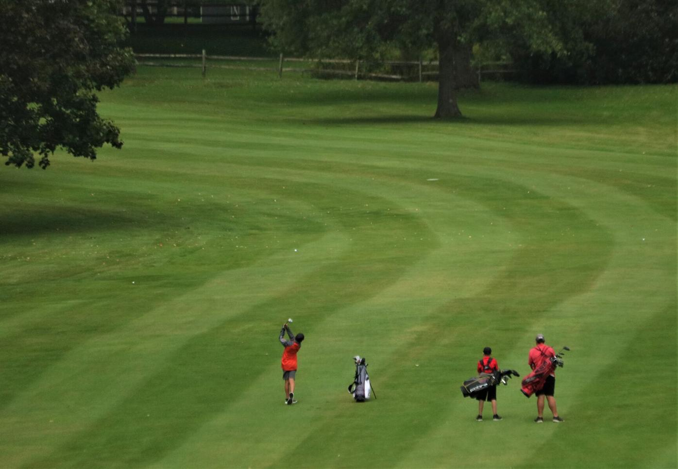 Golfers hit from the fairway