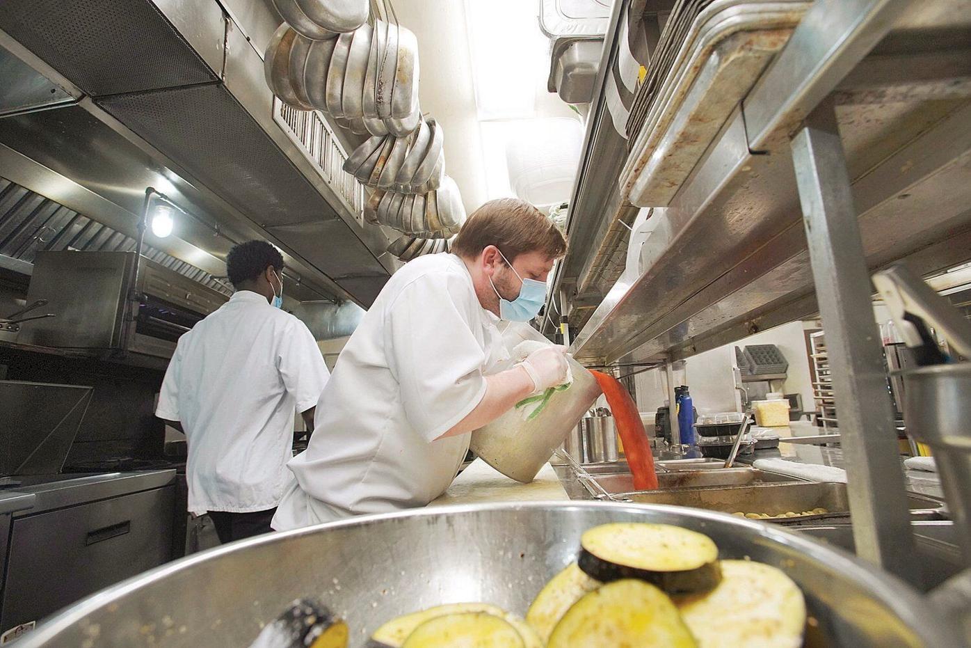 Staff prepare takeout meals at Mazzeo's Ristorante in the spring
