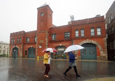 Two women walking with umbrellas in rain