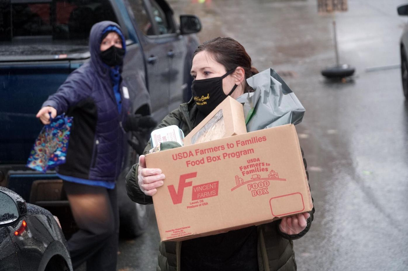 Volunteer loading box of food into cars outside