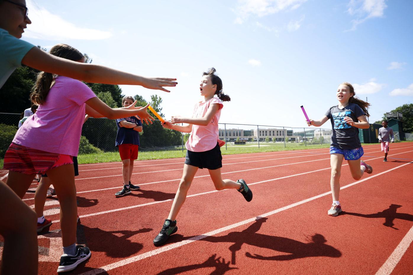 kids pass batons in relay race