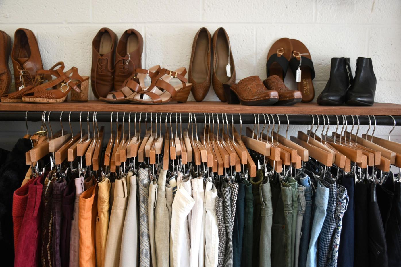 Des chaussures sont posées sur un étalage de vêtements sur des cintres