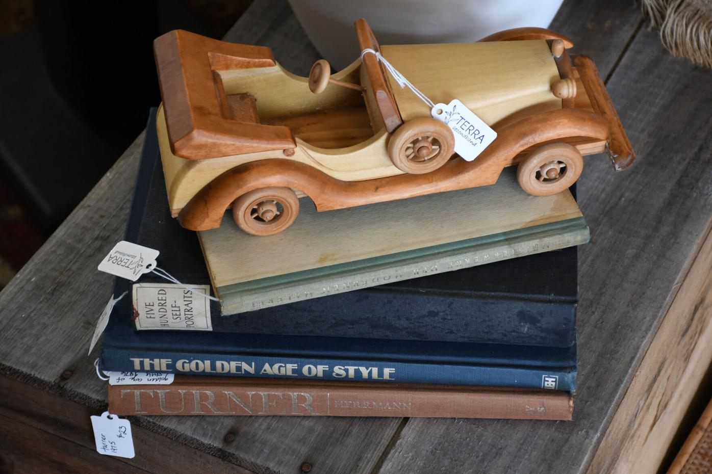 Une voiture en bois est assise sur une pile de livres vintage