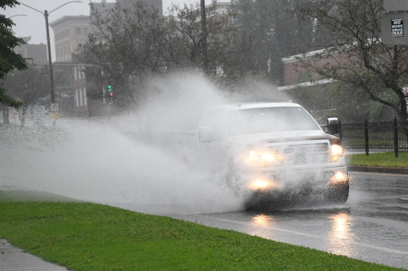 An SUV splashes through a puddle