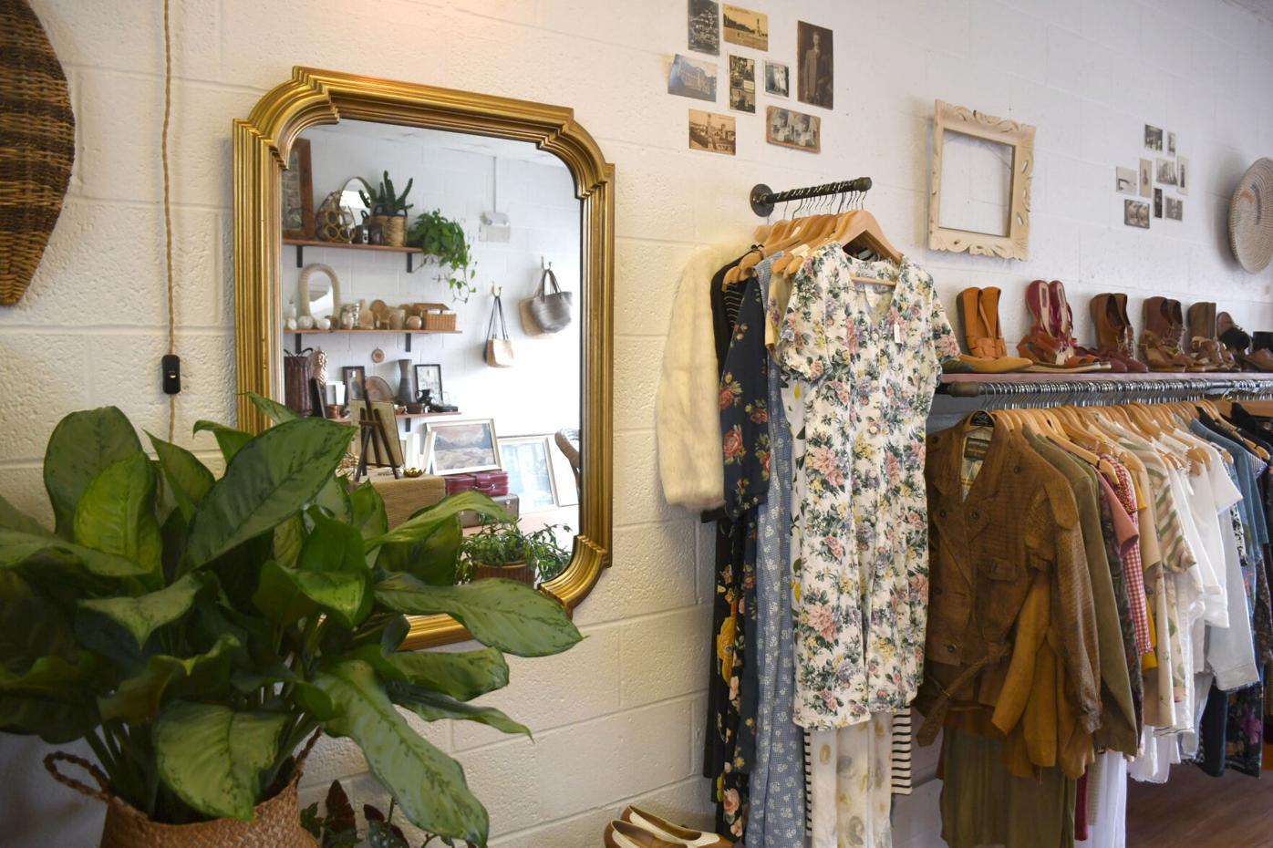 Un miroir reflète les articles dans le magasin alors que les vêtements et les chaussures sont affichés à droite