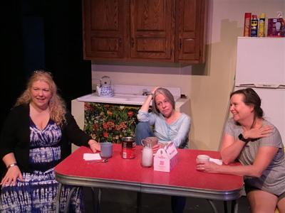 Three women sit at a table