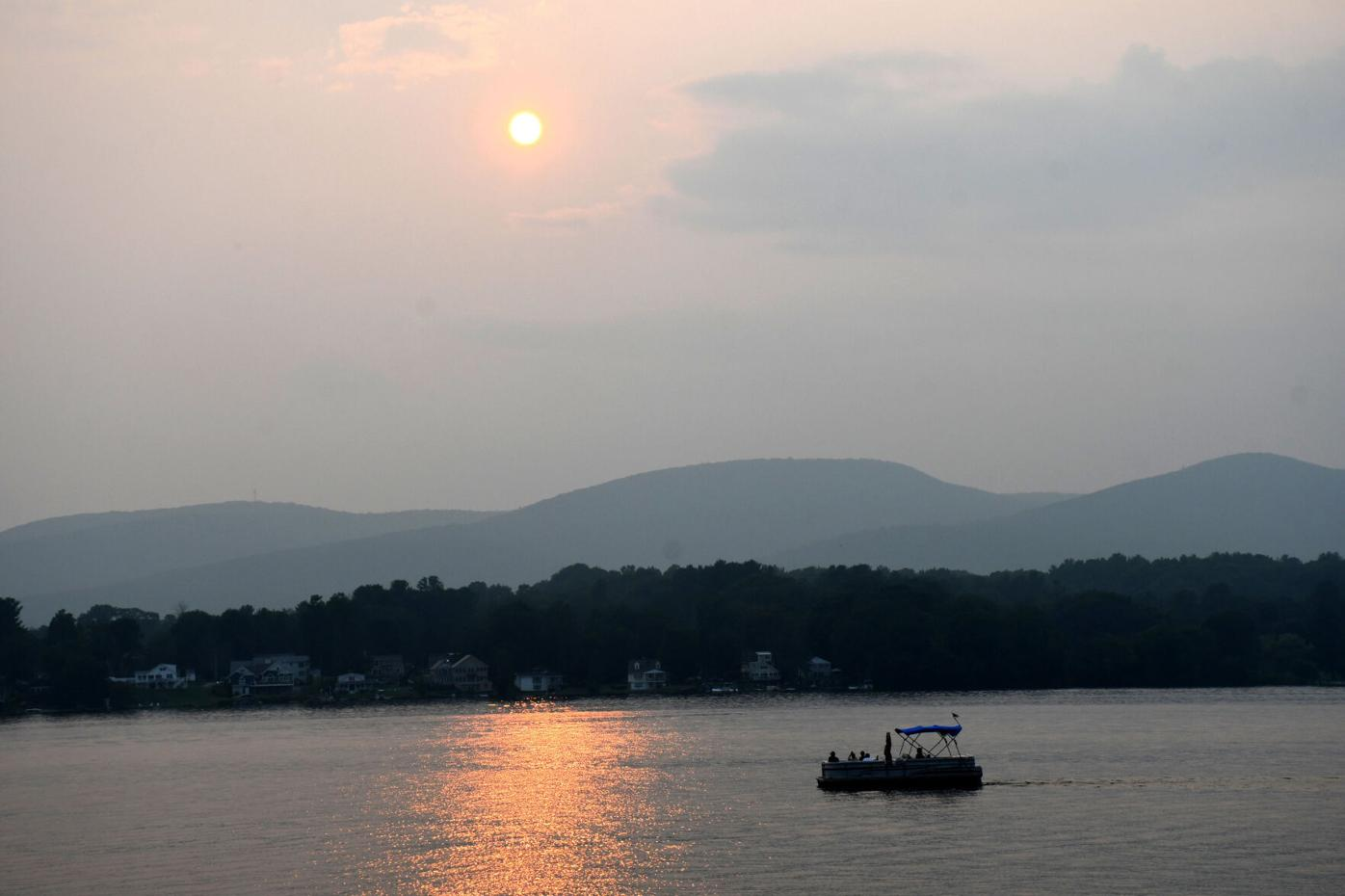 Sun sets over lake with boat in foreground