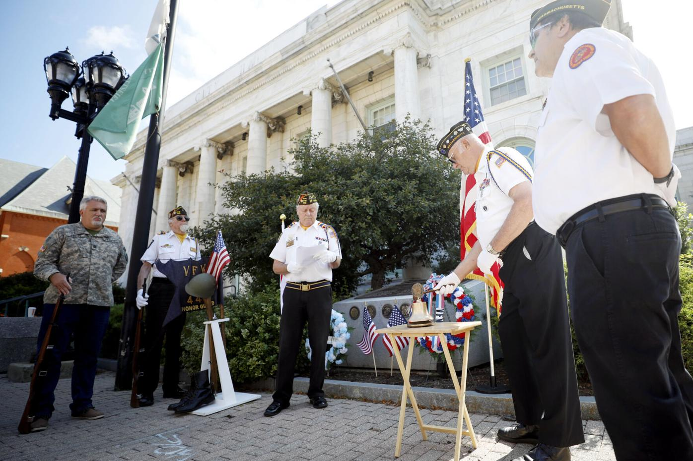 veterans stand together and ring small bell