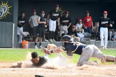 Runner tagged out at home as he slides into plate